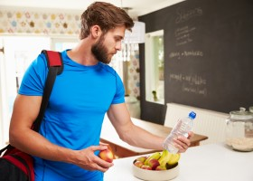 Man Wearing Gym Clothing Choosing Fruit From Bowl