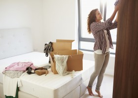 31010064_l-Woman-Moving-Into-New-Home-And-Unpacking-Boxes-In-Bedroom